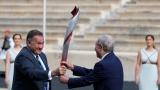 Spyros Kapralosa remis la torche olympique à Yu Zaiqing