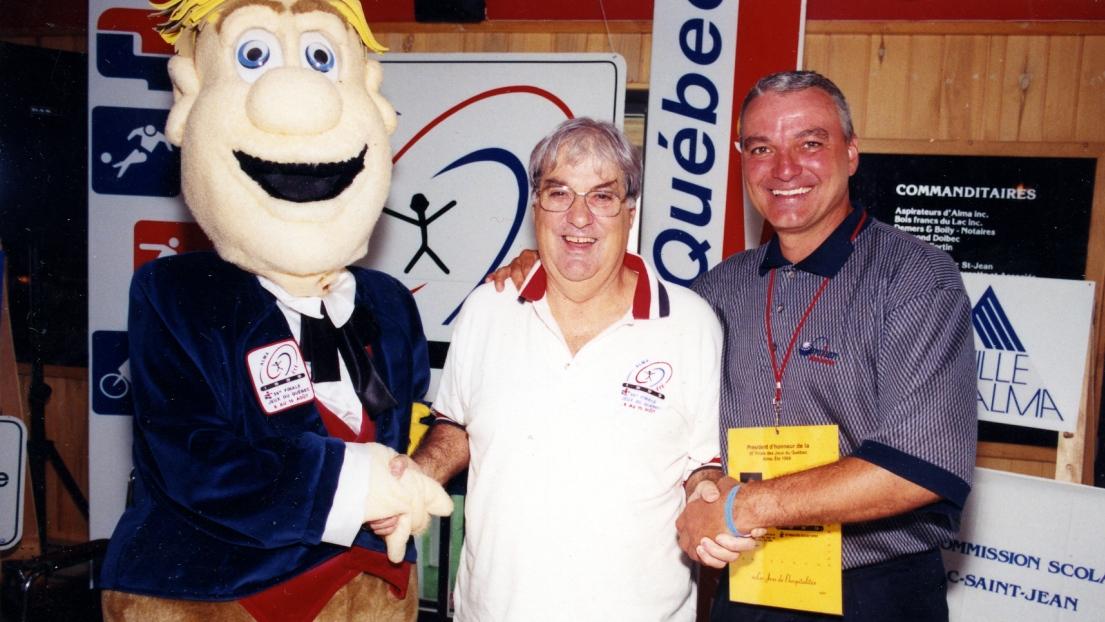 Jean-Claude Lindsay en compagnie de Mario Tremblay et de la mascotte des Jeux du Québec de 1999.