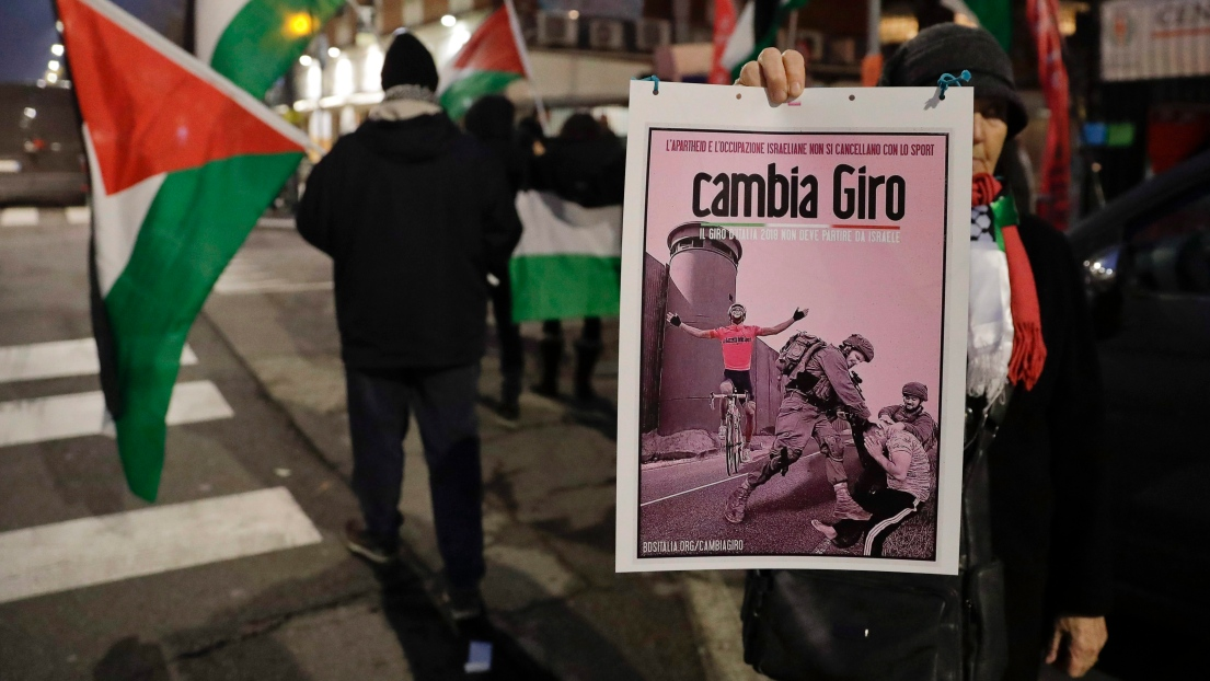 Un petit groupe de personnes manifestent avec des drapeaux palestiniens