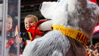 La mascotte des Flames, Harvey the Hound, s'amuse avec un jeune fan au Scotiabank Saddledome