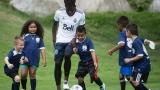 Des enfants jouant au soccer avec Alphonso Davies