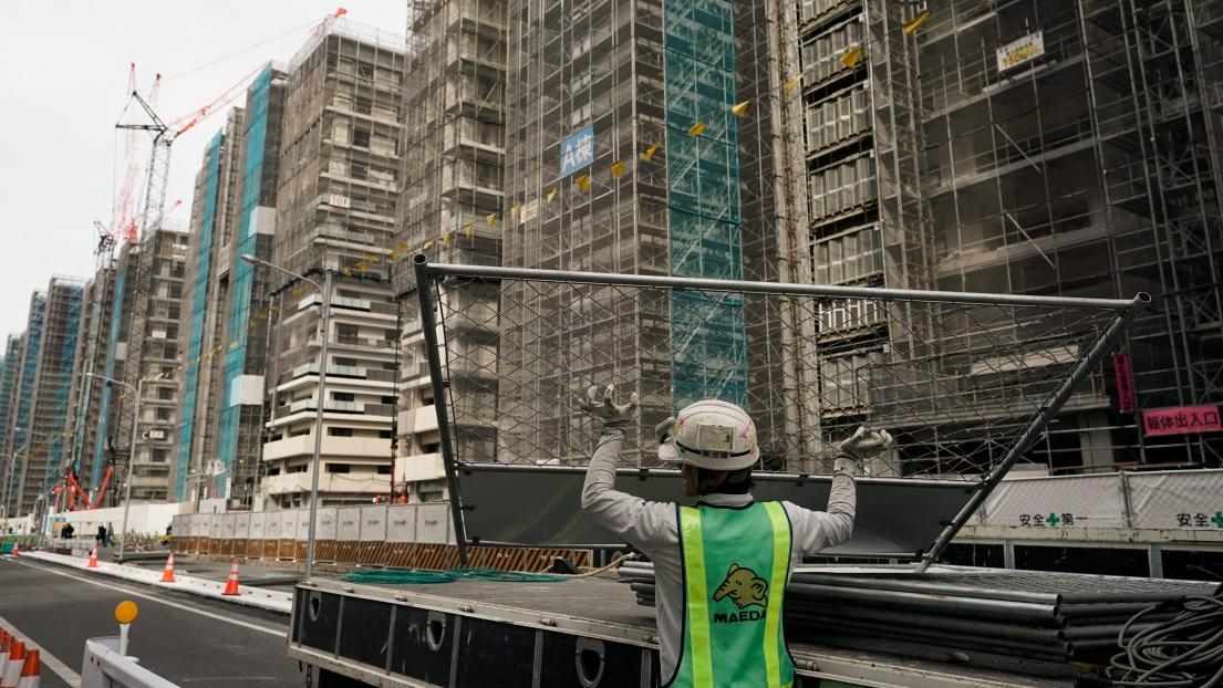 Un ouvrier en plein travail sur le site du village olympique de Tokyo